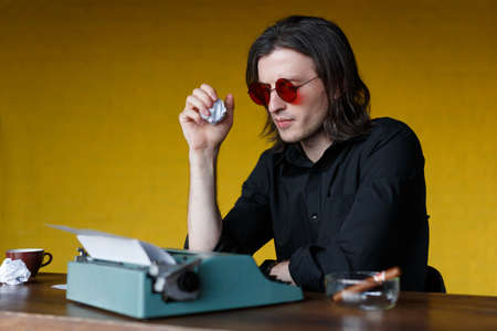 Profile of a young writer in red glasses with gray long hair, dressed in black shirt, working hard, creates his own creation, crumpled sheets of paper in hand over yellow background.