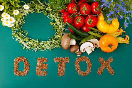 Top view of inscription detox from laxseed combination with fresh colorful vegetables veg, on a green background. Various vegetables, micro plants, nutritions. Space for text.