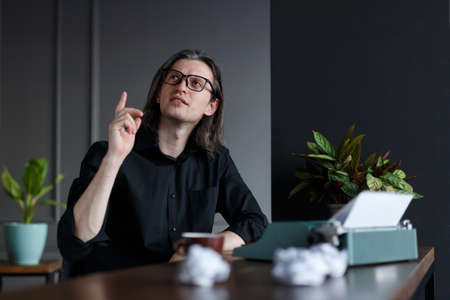 Portrait of a man in black shirt, with long hair, raised his finger up show have a ideea, seated at a table near typewriter in his office. A writer searching a inspiration, over gray background.