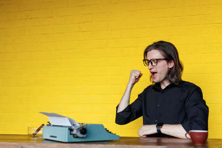 Young man in black shirt, with long hair, raised his hand up show have a successful, seated at a table near typewriter in his office. A writer searching a inspiration, over yellow background. Imagens
