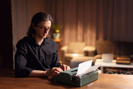 Portrait of a cheerful man, a writer working on a his new book. Confident man in black shirt and eyeglasses, seated at a table near typewriter, over blurred dark interior. Imagens