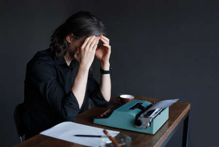 Young man writer in black shirt with long gray hair, in eye glasses, sitting at a table and looking on a typewriter, lack of inspiration, meditates concept. Copy space.