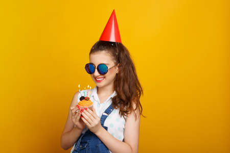 Girl in sunglasses holding in hands a cupcake with candles. Teenager with birthday cupcake on yellow background.