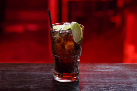 Closeup of a Cuba Libre cocktail in short glass, gin, standing on the bar counter, isolated on a red light background.