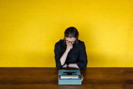In search of inspiration. Thoughtful mature man holding hand under the chin, looking on down on a typewriter while sitting at his working place in office, over yellow background. Imagens
