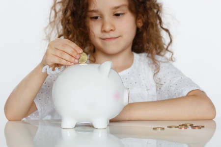 Closeup portrait of a cute curly girl in white putting coin into piggy bank, beside a lot of coins, over white background.