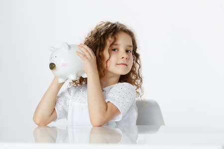 Pretty curly little girl holding a piggy bank, keeping up her ear to listen, over white background. Educational, saving money concept. Imagens