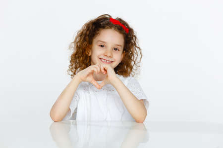 Cute curly little girl in studio, seated at a table, showing heart shape with hands, isolated on a white backgrounds.