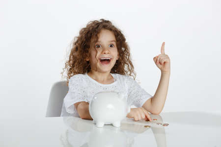 Curly little girl seated at a table near piggy bank, showing a finger up, over white background. Copy space. Finance, fund concept. Imagens