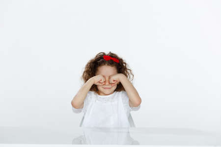 Portrait of a cute little girl in white t-shirts, seated at a table, rubbing his eyes with hands over white background. Copy space. Imagens
