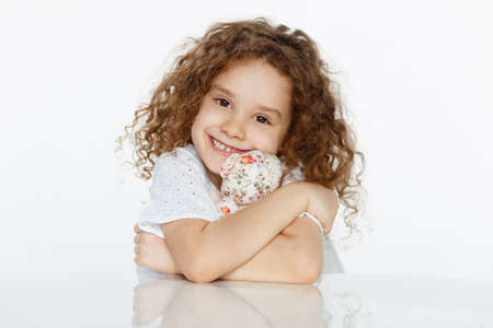 Adorable little cute girl with curly hair in white, seated at a table, looking at camera, over white background.