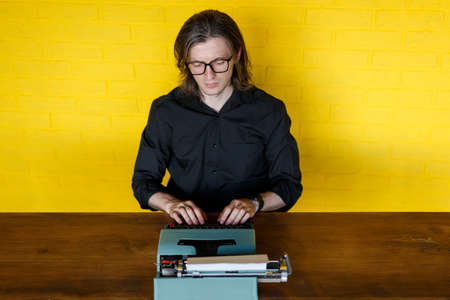 Frontal portrait of a writer sitting at table working on a typewriter, over yellow wall.
