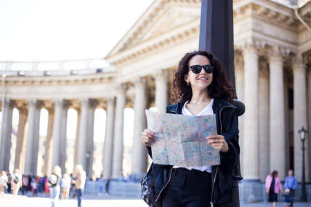 Cheerful young woman with curly hair, in sunglasses with a city map in hands, looking on a historic city, have a backpack, over cathedral background.