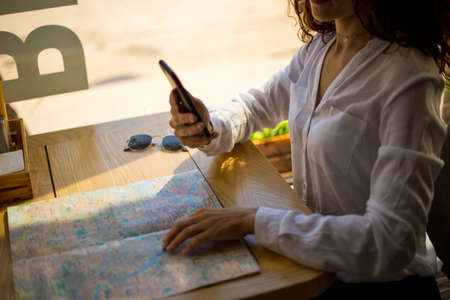 Close up of women holding cell telephone and searching on paper map a destination, uses mobile phone in cafe