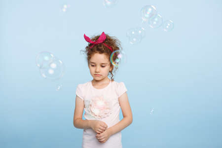 Indisposed little curly girl, looking down in summer outfit, over light blue background, posing in studio, Soap bubbles fly near kid. Emotional mood. Reklamní fotografie
