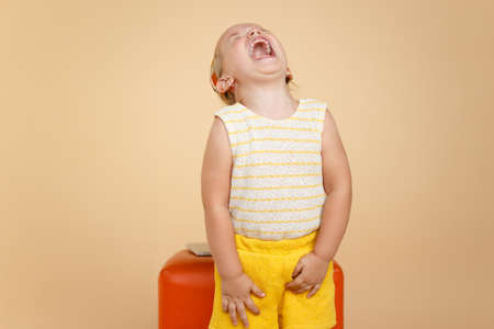 ortrait of a little funny toddler girl screaming, over beige background. Horizontal view. Copy space.