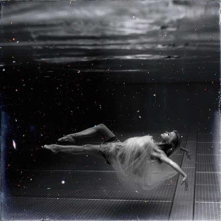 Black and white image. Underwater photo beautiful blonde wearing in white flying dress, swimming in pool underwater. 版權商用圖片 - 132752817