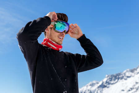 Portrait of a handsome young man skier arranged his ski glasses, looking at a side, isolated on a clear sky and peak mountain background.
