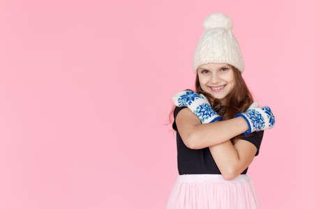 Niña de retrato frontal con sombrero blanco y guantes, abrazó con las manos, sobre fondo rosa en estudio. Foto de archivo