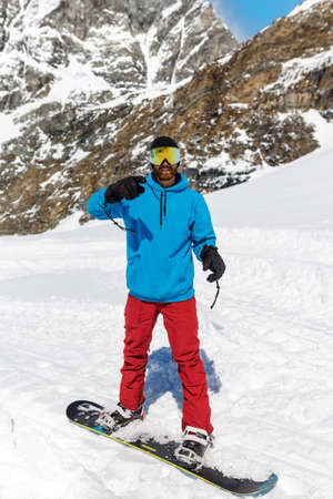 A young man equipped in ski clothes with ski goggles, skiing in a mountain, on beautiful landscape background. Winter sport, snowboarding. Vertical view.