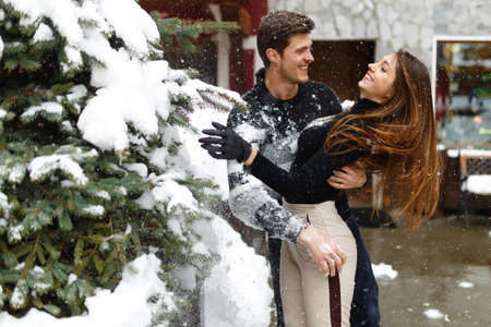 Loving young couple in winter clothes hugging and smiling outside, in a small town in Italy. horizontal image, winter view.