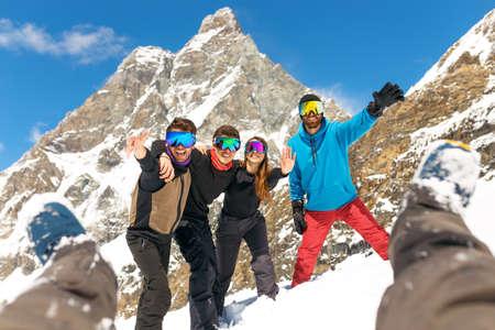 Groupe de personnes heureuses dans l'équipement de ski, s'étreindre ensemble, regarder la caméra, avoir la station de ski Winter Mountain. Banque d'images