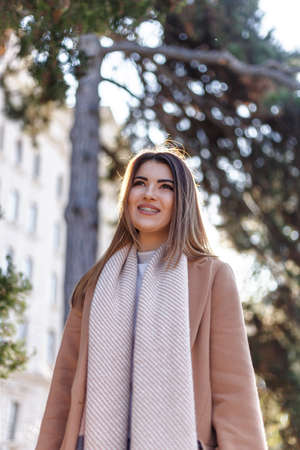 Beautiful young female model hes walking in park , autumn season. Pretty girl with coat outdoors in fall with smiling.