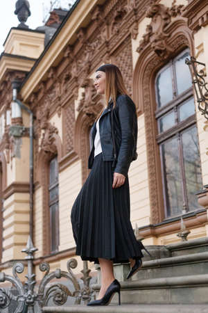 A woman walking down stairs, near old building, in elegant outfit, looking at side, in black leather jacket and high heels. Vertical view. Reklamní fotografie