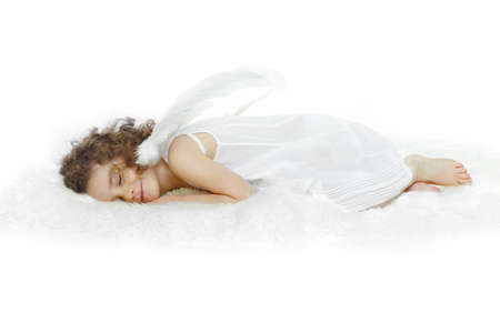 Little girl with curly hair, in white dress and wings, sleeping on white fur, studio shooting.