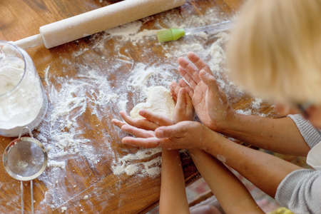 Cropped image of a female and kid hands holding dough in heart shape top view. Baking ingredients on the dark wooden table. Horizontal view.