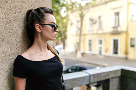Profile of a young sexy brunette woman in sunglasses, dressed in slim black dress, supported by the wall on the balcony, urban street.