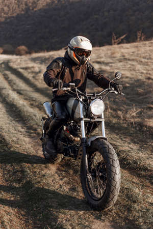Outdoors portrait of a motorcyclist equipped with helmet and protective clothing, who drives a motorcycle on a steppe path at sunset.