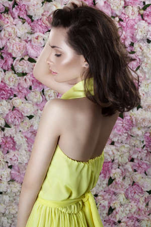 Beauty portrait. A gorgeous young woman with makeup, turned in a profile, which is near the wall of flowering peony.
