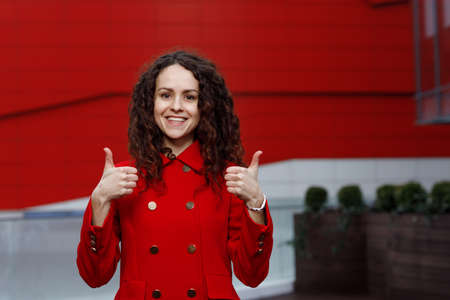 Smiling pretty brunette curly young woman in red suit, showing thumbs up isolated on the red building background.