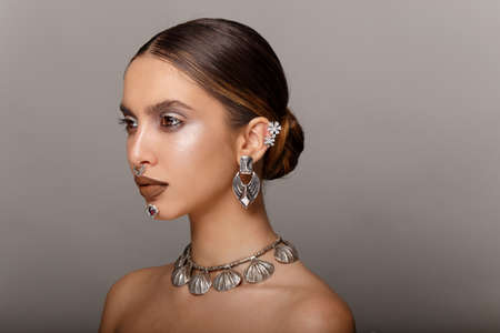 Fashion girl beauty portrait. Young woman with jewelry, hair arranged, makeup, looks to the side, with bare shoulders. Space for text.