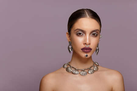 Beauty Portrait of a beautiful fashion girl with sensual marsala lips, make-up, jewelery, hairstyle. Copy space.