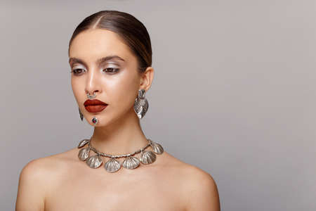 Beautiful with sensual lips, arranged, with jewelry, tight hair, looks down, with bare shoulders, over grey background.
