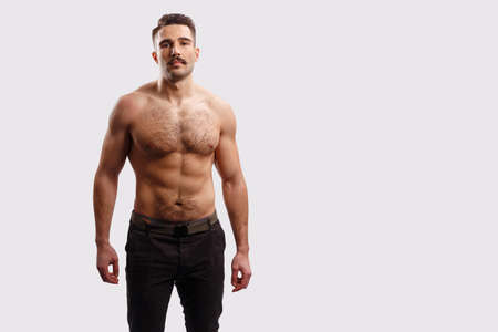 Portrait of a handsome bearded man with torso, looking at camera over white background. Horizontal view. Stock Photo