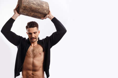 Handsome man with moustache, with naked torso rise up a tree trunk above the head, looking down, over white background. Banco de Imagens