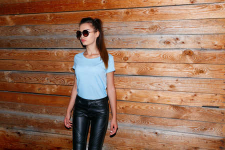 Stylish hipster girl in hat, wallking in the city at night, wear in round sunglasses is supported by a wooden wall.