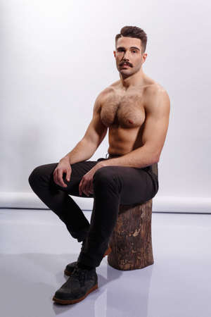 Man with moustache, shirtless, muscled body, biceps and triceps, seated on a tree trunk, white background.