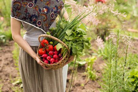 Primer plano de una agricultora sosteniendo una canasta de verduras. Vista horizontal.