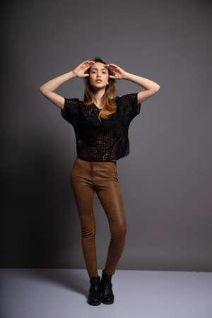 Full-length portrait of cheerful girl on dark background. Beautiful female model having fun during photoshoot in studio.