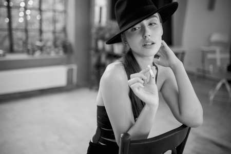 Portrait of beauty portrait of a elegant young woman in black hat smoking a cigaret in room, image black and white.