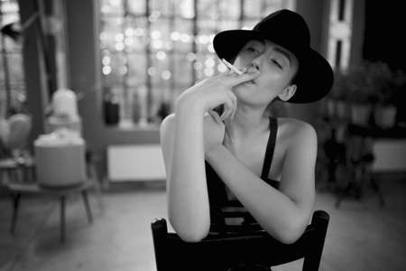Smoking girl in elegant clothes and hat, seated on chair, looking at camera. Black and white image.