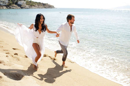 A beautiful couple just got married, enjoying running on the beach, husband holding his wifes hand.