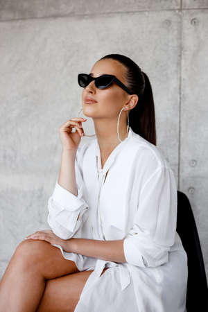 Vertical view. Profile portrait of a girl with round earrings, her hair in a ponytail and black sunglasses in a white shirt, looking sideways in a concrete gray background.