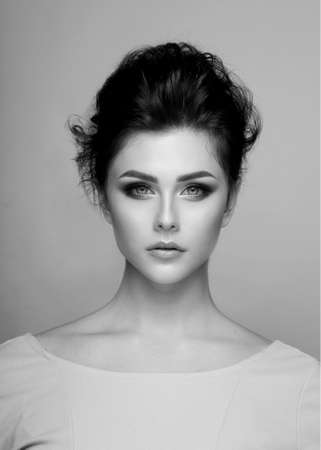 Portrait of beauty fashion model with superb makeup looking at camera. Photo black and white.