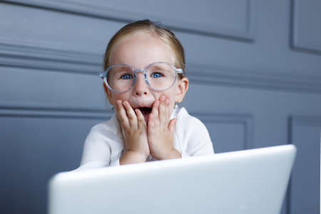 Portrait of little girl in eyeglasses behind laptop computer, making mimic with her hands, over on a grey background. Фото со стока - 147270704