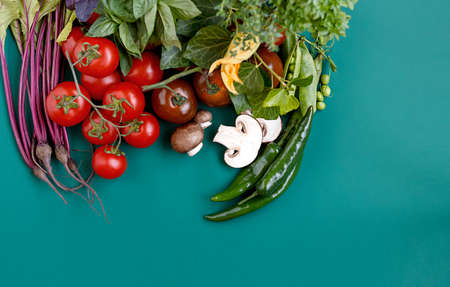 Horizontal view. Top view of a various colorful vegetables arranged on green background. Place for text, copy space. Banco de Imagens